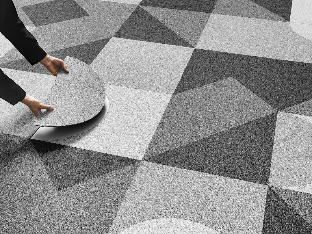 pessoa realizando a troca de uma placa do carpete modular