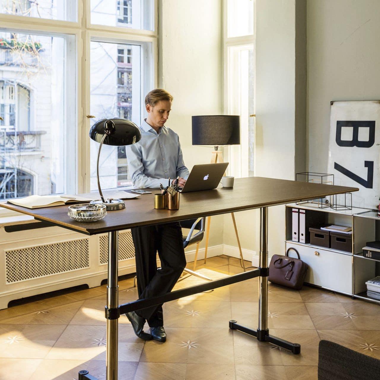 pessoa trabalhando em pé na mesa com altura regulável